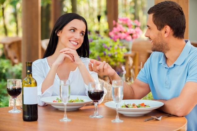 Наслаждаясь каждой минутой близости с ним. красивая молодая влюбленная пара разговаривает и улыбается во время отдыха в ресторане на открытом воздухе вместе