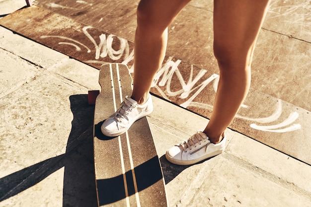 Наслаждаюсь каждой минутой лета. крупный план молодой женщины, держащей одну ногу на скейтборде, проводя время на открытом воздухе