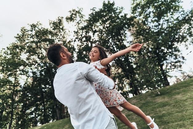 Наслаждаемся каждой минутой вместе. молодой любящий отец несет свою улыбающуюся дочь, проводя свободное время на открытом воздухе