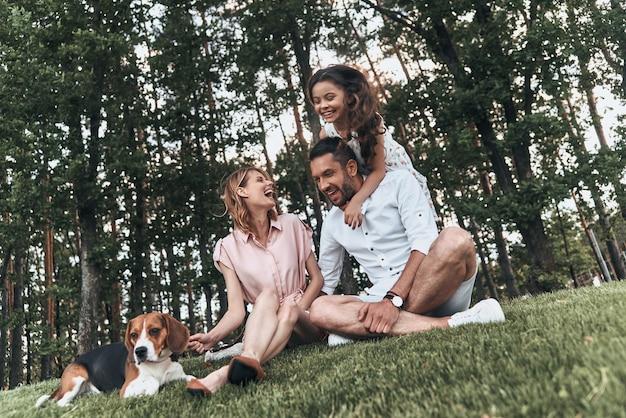 Наслаждаемся каждым моментом вместе. счастливая молодая семья из трех человек с собакой улыбается, сидя на траве в парке