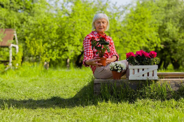 Enjoying flowers. grey-haired woman sitting near trees in her garden and enjoying flowers