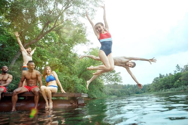 友達と森のパーティーを楽しんでいます。一緒に川で泳いでいる美しい幸せな若い男性と女の子のグループ。夏、パーティー、冒険、若者、友情の概念