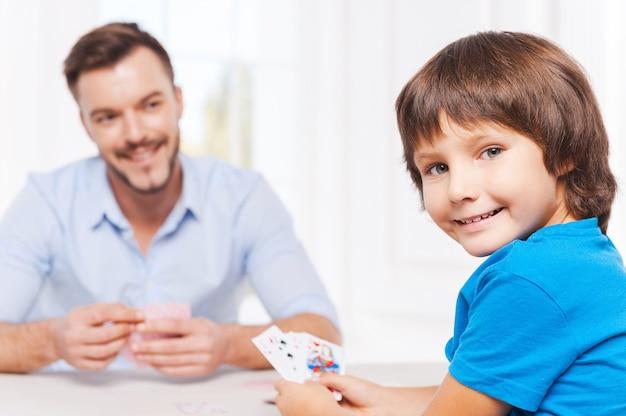 Проводим вместе свободное время. счастливый отец и сын, играя в карты и улыбаясь