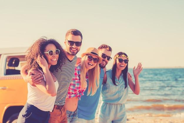 Наслаждаясь свободой. группа веселых молодых людей, обнимающихся и смотрящих в камеру во время прогулки по пляжу