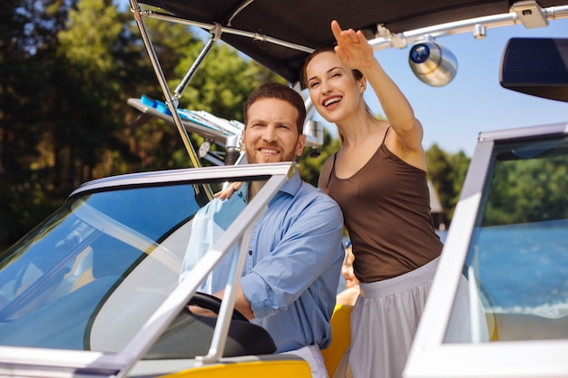 自由を楽しんでいます。女性が島を指差しながらボートを航海し、次の目的地を選択する明るい若いカップル