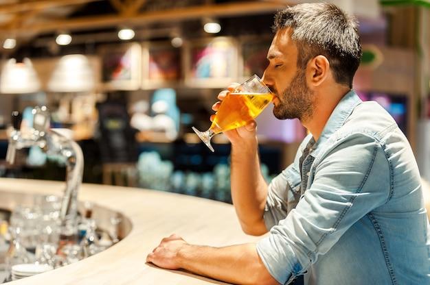신선한 맥주를 즐기고 있습니다. 바 카운터에 앉아 맥주를 마시고 눈을 감고 있는 젊은 남자의 측면 보기