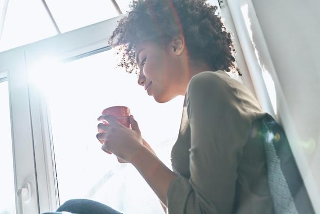 淹れたてのコーヒーを楽しんでいます。カップを持って、屋内の窓の近くに座って笑っている魅力的な若いアフリカの女性
