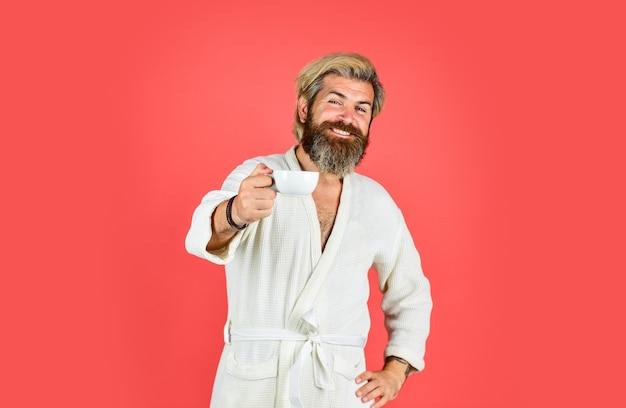 淹れたてのコーヒーを楽しんでいます。毎朝コーヒーから始まります。バスローブの学士号。ドレッシングガウンのひげを持つ男。お風呂の服を着た男がコーヒーを持っています。朝の儀式の概念。コーヒーを飲む疲れた男。