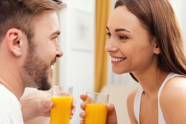一緒にフレッシュジュースを楽しんでいます。オレンジジュースとグラスを保持し、笑顔でお互いを見ている美しい若い愛情のあるカップル