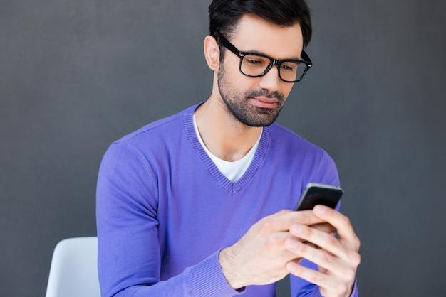 良いメッセージを楽しんでいます。灰色の背景に座っている間携帯電話を保持しているハンサムな若い男