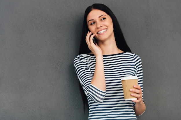良い話と温かい飲み物を楽しんでいます。コーヒーカップを持って、携帯電話で話し、立っている間笑顔の魅力的な若い女性