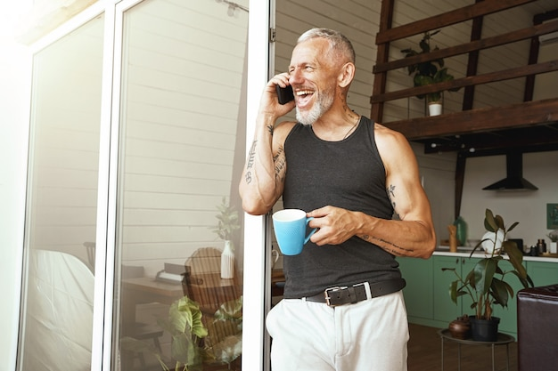 Enjoying good talk happy middle aged caucasian man talking by mobile phone and laughing while