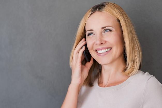 良い話を楽しんでいます。携帯電話で話し、笑顔でうれしそうな成熟した女性