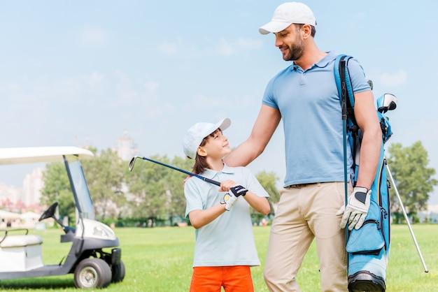 一緒に素晴らしいゲームを楽しんでいます。ゴルフ場に立っている間、お互いを見つめている若い男と彼の息子の笑顔