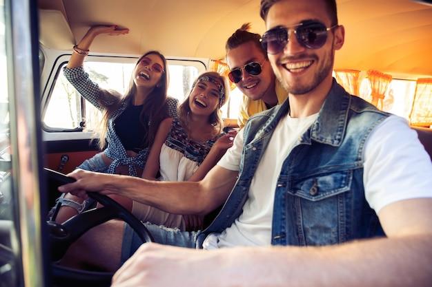友達と素晴らしいロードトリップを楽しんでいます。ミニバンの中に座って楽しんでいる陽気な若者のグループ。