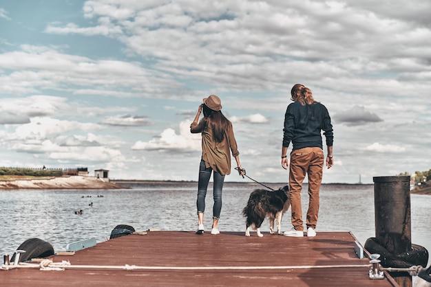 Наслаждаясь прекрасным видом. полная длина вид сзади красивой молодой пары с собакой, стоящей на деревянной платформе, проводя время у реки