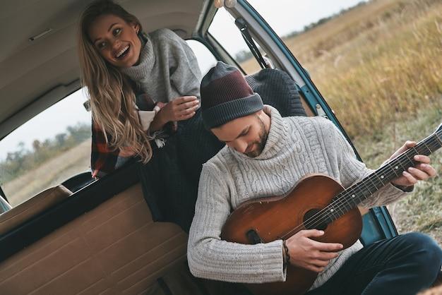행복한 순간을 즐기고 있습니다. 복고 스타일의 미니 밴에 앉아 아름다운 여자 친구를 위해 기타를 연주하는 잘생긴 청년