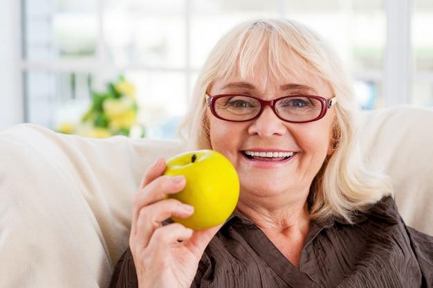 건강한 식생활을 즐기고 있습니다. 사과를 들고 의자에 앉아 웃고 있는 시니어 여성