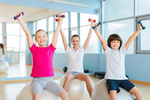 健康的なライフスタイルを楽しんでいます。健康クラブでフィットネスボールに座ってダンベルで運動する陽気な母親と2人の子供