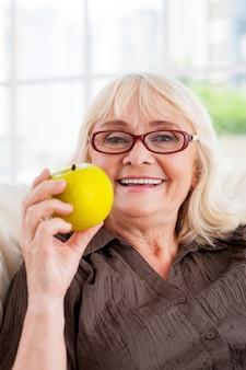 건강한 라이프 스타일을 즐기고 있습니다. 사과를 들고 의자에 앉아 카메라를 바라보는 쾌활한 시니어 여성
