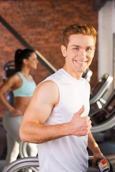 Наслаждаемся здоровым образом жизни. красивый молодой человек показывает большой палец вверх и улыбается во время прогулки на беговой дорожке с женщиной, бегущей на заднем плане