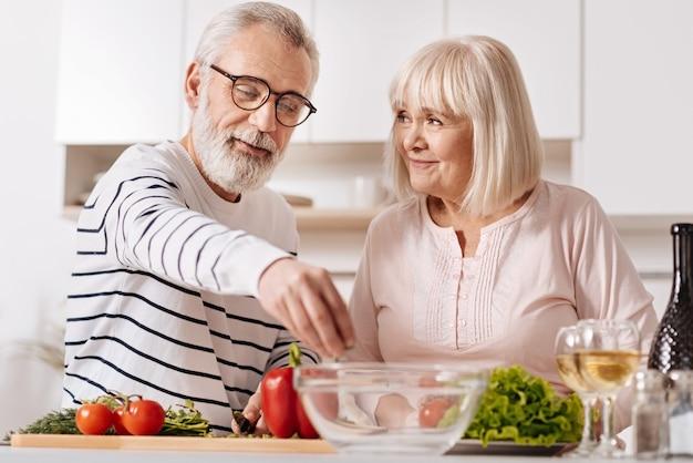 健康的な栄養を楽しんでいます。キッチンに立って、ケアと愛を表現しながら健康的な夕食を調理する活気のある慎重な明るい年配のカップル