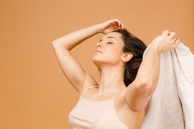 Наслаждаясь ее красотой. привлекательная молодая женщина в нижнем белье позирует пока полотенце сушит волосы, стоя изолированными на бежевом фоне.