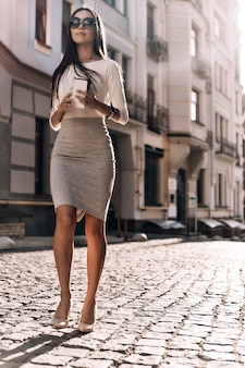 Enjoying her coffee break. full length of attractive young woman holding her smart phone and disposable cup while walking outdoors