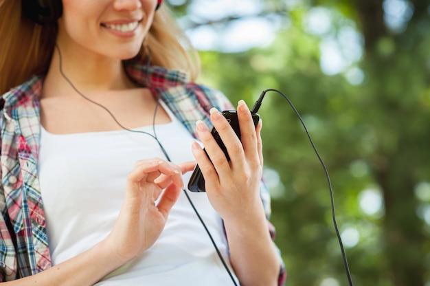 그녀가 좋아하는 음악을 야외에서 즐깁니다. 헤드폰을 끼고 공원에서 나무에 기대어 음악을 듣고 웃고 있는 아름다운 젊은 여성의 이미지