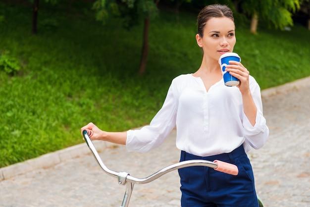 公園で彼女の自由な時間を楽しんでいます。コーヒーを飲みながら、公園で自転車を持って歩きながら目をそらす魅力的な若い女性