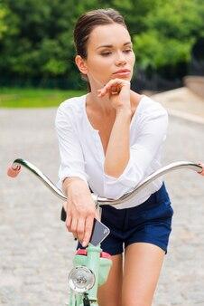 Наслаждаясь своим свободным временем в парке. привлекательная молодая женщина пьет кофе и смотрит в сторону во время прогулки на велосипеде в парке
