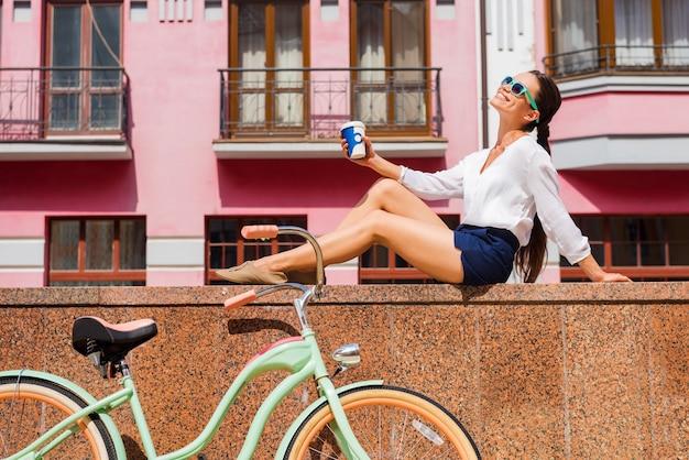 町での彼女の自由な時間を楽しんでいます。屋外と彼女のビンテージ自転車の近くに座っているファンキーなサングラスで美しい若い笑顔の女性