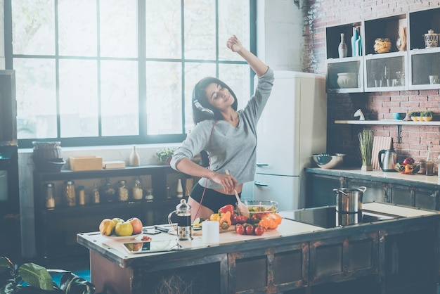 Enjoying her morning. beautiful young mixed race woman in headphones cooking salad and dancing while standing in kitchen at home