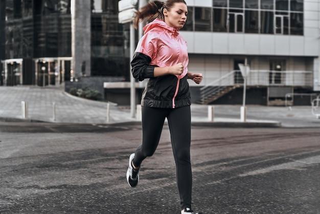 彼女の走りを楽しんでいます。通りに沿って走っているスポーツ服の魅力的な若い女性の全長