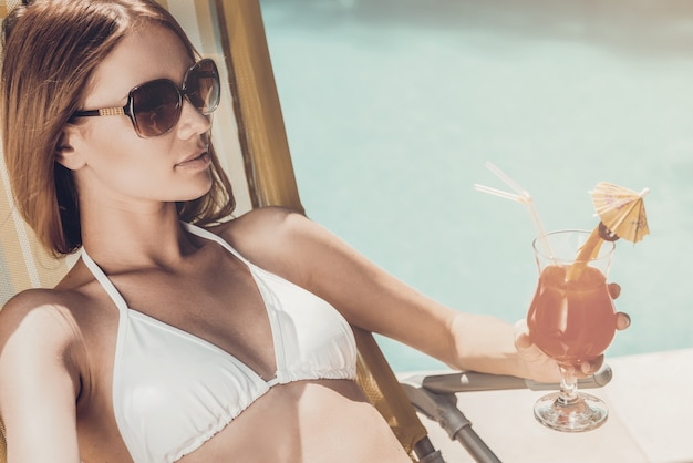 Enjoying her summer vacation. beautiful young woman in white bikini holding glass with cocktail while relaxing in deck chair near the pool
