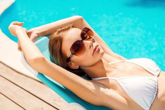 彼女の夏休みを楽しんでいます。プールの近くのデッキチェアでリラックスした白いビキニの美しい若い女性の上面図