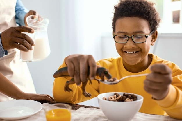 Enjoying himself. pleasant upbeat boy playing with a toy dinosaur and feeding it with cereals while his father pouring him a glass of milk