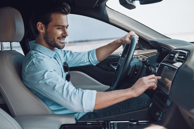 彼のドライブを楽しんでいます。ステータス車を運転しながら笑顔のスマートカジュアルウェアのハンサムな若い男