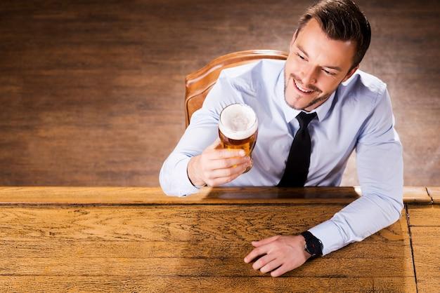 彼の好きなビールを楽しんでいます。シャツとネクタイのハンサムな若い男の上面図は、ビールとガラスを調べて、バーのカウンターに座って笑っている
