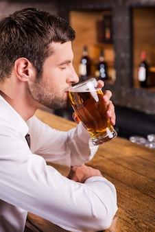 彼のお気に入りのラガーを楽しんでいます。バーカウンターに座ってビールを飲むハンサムな若い男の側面図