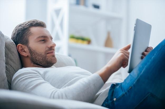 家で余暇を楽しんでいます。デジタルタブレットに取り組んでいるハンサムな若い男の側面図