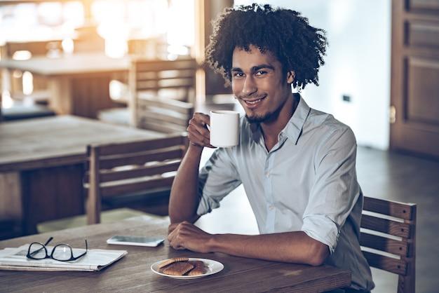 그의 아침을 즐기고 있다. 커피 컵을 들고 미소로 카메라를 보고 있는 젊은 아프리카 남자