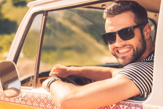 Наслаждаюсь своей поездкой. веселый молодой человек улыбается в камеру и держится за руль, сидя в своем минивэне