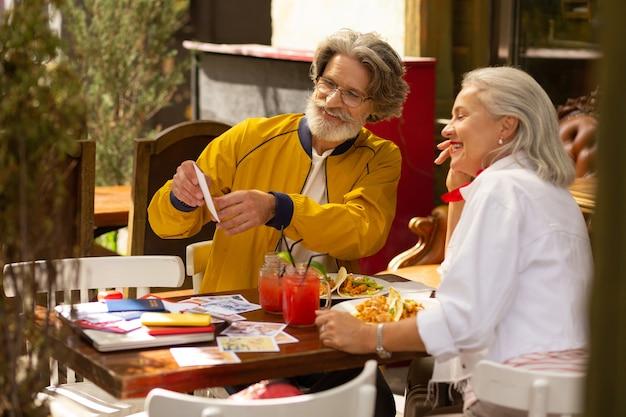 휴가를 즐기고 있습니다. 행복한 부부는 거리 카페에 앉아 휴가 사진을 보고 있습니다.