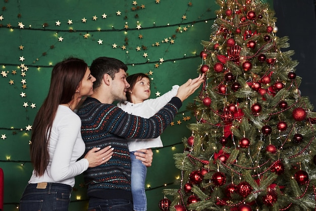 Enjoying the holidays together. happy family celebrating new year and standing near christmas tree.