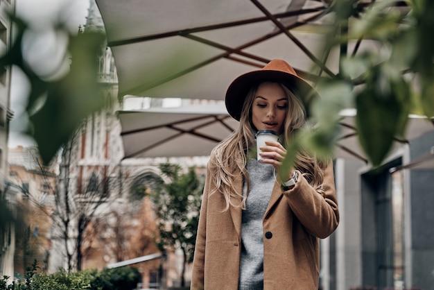 ホットコーヒーを楽しんでいます。屋外に立っている間、コーヒーの匂いを嗅ぐ帽子とコートの魅力的な若い女性