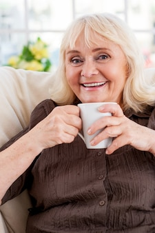 따뜻한 차를 즐기고 있습니다. 컵을 들고 의자에 앉아 웃고 있는 시니어 여성