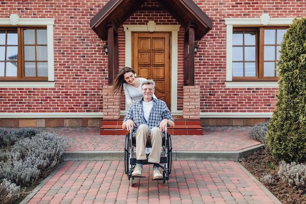 家族の時間で車椅子の老人と庭で笑顔の娘を楽しんでいます