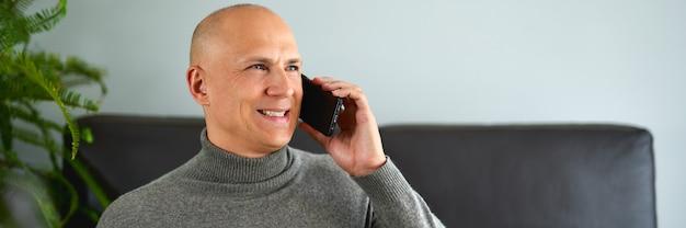 Наслаждайтесь отдыхом дома. радостный человек разговаривает по мобильному телефону на диване