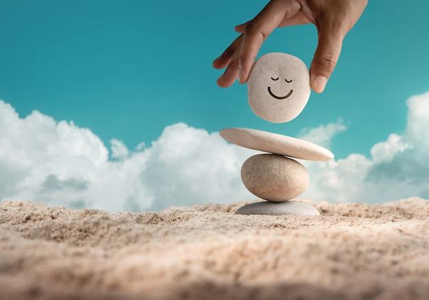 ライフコンセプトを楽しんでいます。調和とポジティブマインド。ビーチの砂の上でバランスをとるために笑顔の漫画と自然な小石の石を設定する手。体、心、魂、精神のバランスを取ります。メンタルヘルスの実践